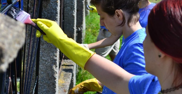 Volunteers painting a fence